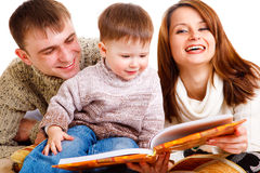 Reading a book. Parents reading a book to their lovely kid Stock Photos