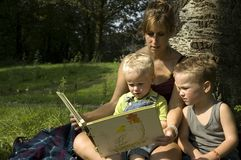 Reading a book. Family reading a book while on a summer trip royalty free stock photography