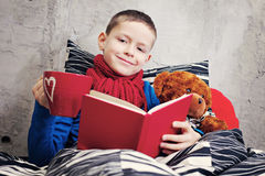 Reading book. 9 years old boy ill reading book in bed - kids and family stock image