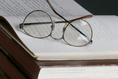 Reading a book. Eye glasses set on top of a open page stock images