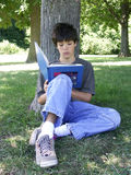 Reading a book. Teen boy reading a book royalty free stock photos