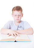 Reading a book. Boy in glasses with a book on a white background Royalty Free Stock Photos