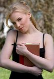 Reading book. Pretty blond woman reading book in a park Stock Images