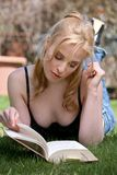 Reading book. Pretty blond woman reading book in a park Royalty Free Stock Photography