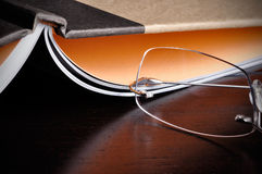 Reading a Book. Eyeglasses next to an open book on top of a wood table Royalty Free Stock Photos