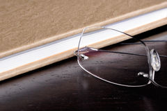 Reading a Book. Eyeglasses next to a book on top of a wood table Royalty Free Stock Photos