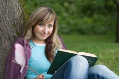 Reading a book. Cute girl is sitting under the tree and reading the book royalty free stock photo