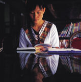 Reading book. It is oriental girl at reading book. it is symmetrical image, the table reflects the girl Stock Images