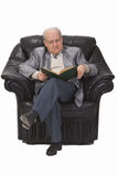 Reading a book. Senior man sitting in an armchair and reading a book.Shot with Canon 70-200mm f/2.8L IS USM Stock Images