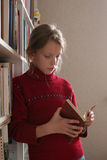 Reading a book. A girl standing near the bookshelf reading a book Royalty Free Stock Photo