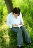 Reading book. Young girl reading book in park Royalty Free Stock Image