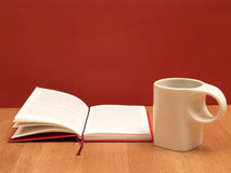 Reading a book. Open book and teacup on a wooden table against red wall Royalty Free Stock Images