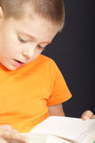 Reading book. Portrait of boy in orange reading book Royalty Free Stock Images