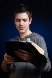 Reading The Book. Young man reading and studying in his Bible royalty free stock image
