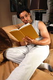Reading Book. A man sits on his couch reading a book Royalty Free Stock Photo