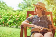 Reading book activity. Concept. Young hispanic woman with book in hand sitting at summer terrace royalty free stock photography