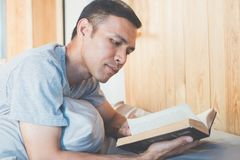 Reading book. Asian man reading a novel in his bedroom Royalty Free Stock Photo