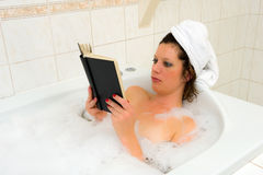 Reading book in bath Royalty Free Stock Image