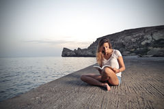 Reading a book at the beach Stock Images