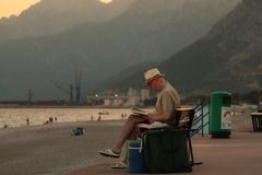 Reading book in beach. He is reading book in Konyaalti Beach from Antalya Stock Photo