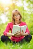 Reading a book. Beautiful mature woman.Happy woman reading a book during springtime in nature Stock Photos