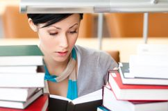 Reading book beautiful student. Reading book female student surrounded with piles of books sitting at the desk at the library. Academic achievement Royalty Free Stock Image