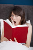Reading a book. Beautiful young woman reading a book with a astonish expression Stock Images