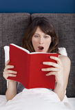 Reading a book. Beautiful young woman reading a book with a astonish expression Royalty Free Stock Image