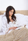 Reading book on bed Royalty Free Stock Images