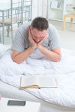 Reading book in bed Stock Photo