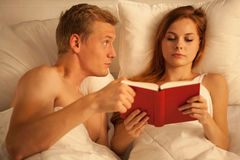 Reading book in bed Stock Image