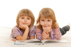 Reading a book on the carpet at home. Two pretty little girls are reading a book on the carpet; isolated on the white background Royalty Free Stock Photos