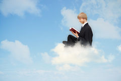Reading book on the cloud. Business man reading book on the cloud Royalty Free Stock Photos