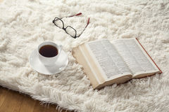 Reading book with coffee on carpet Royalty Free Stock Images