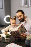 Dark-haired bearded teacher in a striped shirt reading a book with his pupil royalty free stock images