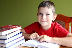 Reading book and doing homework. Eight years old boy reading book and doing homework Stock Photos