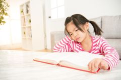Reading book and doing homeworks. Unhappy schoolgirl in stress or depression feel bored at home, reading book and doing homeworks driving her crazy. family Royalty Free Stock Photo