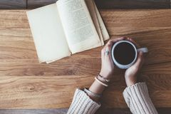 Reading a book and drinking coffee in cafe Stock Photography