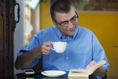 Reading book and enjoying coffee Royalty Free Stock Photo