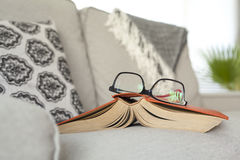Reading book with eyeglasses Stock Photos