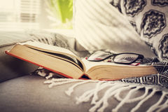 Reading book with eyeglasses on sofa Stock Images