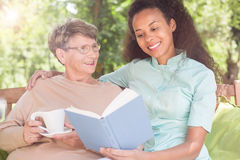 Reading book in the garden. Senior women and caregiver reading book in the garden Royalty Free Stock Images