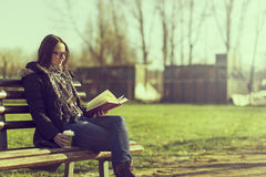 Reading a book. Girl sitting on a wooden bench, reading a book and drinking coffee, outdoors Royalty Free Stock Photos