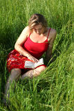 Reading a book in the grass. Reading a book in a field of grass stock photo