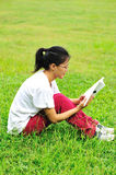 Reading book on grass Stock Photography
