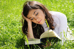 Reading book on grass Stock Photo