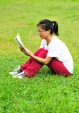 Reading book on grass Royalty Free Stock Photos