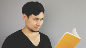 Reading book happily. An asian man with black t-shirt royalty free stock images