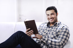 Reading book in home interior. Young man reading book in home interior on white background Royalty Free Stock Photos