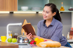 Reading book in the kitchen Royalty Free Stock Photos